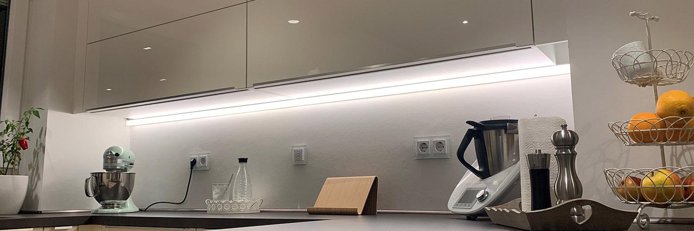 Die Arbeitsflächenbeleuchtung einer modernen und hellen Küche steht im Vordergrund.