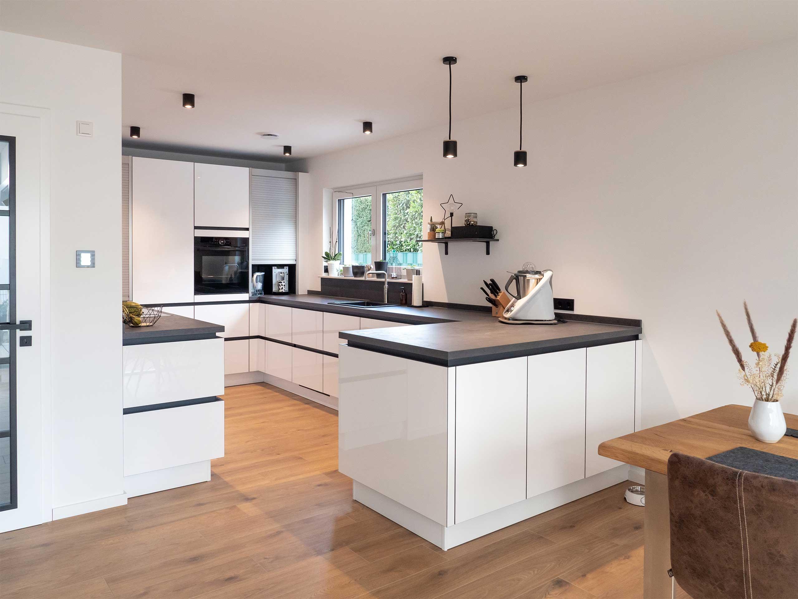 Die Deckenbeleuchtung einer modernen und hellen Küche steht im Vordergrund.
