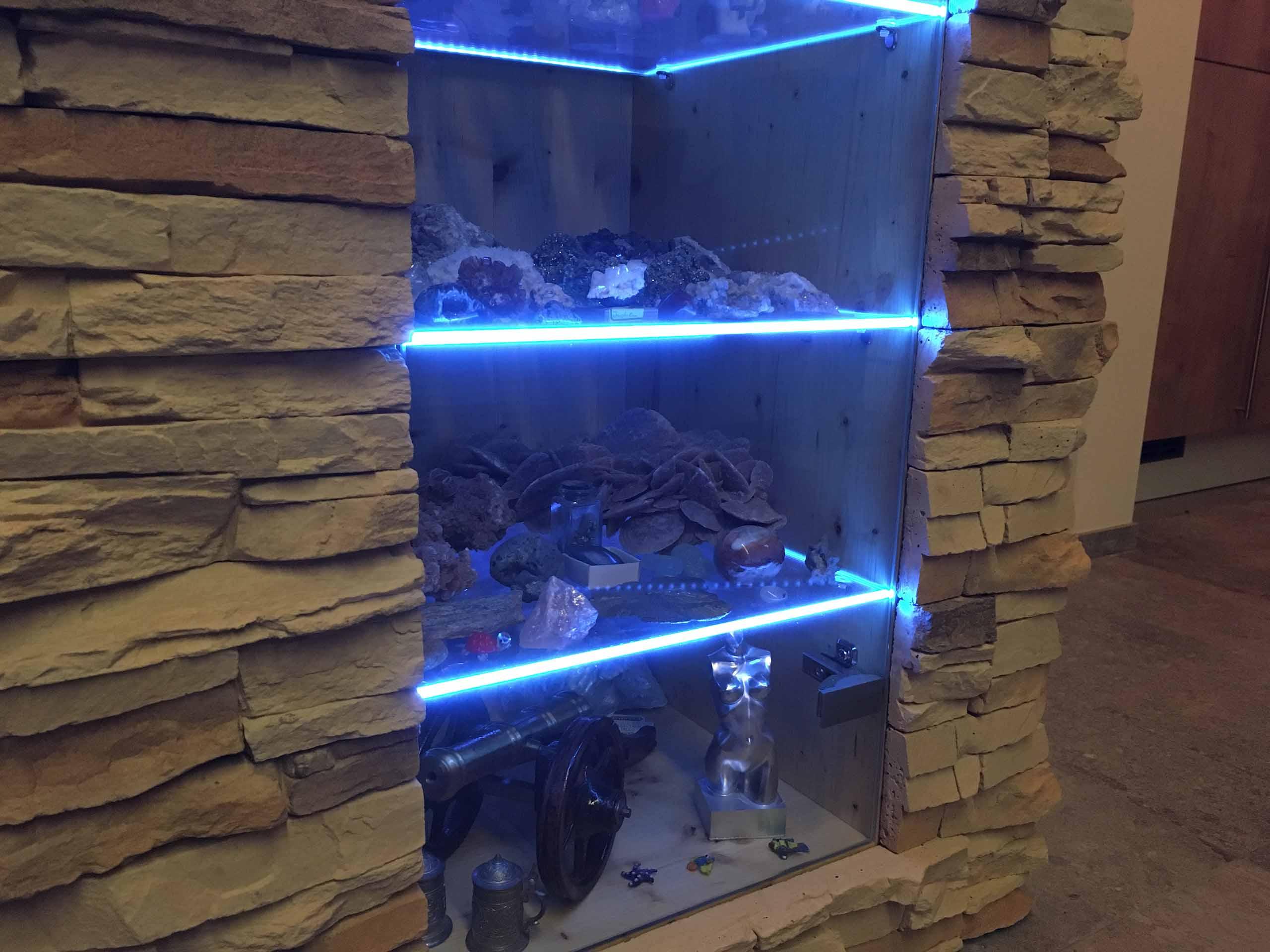 Die farbige LED-Regalbeleuchtung eines modernen Wohnzimmers steht im Vordergrund.